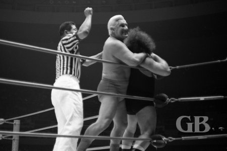 Fred Blassie tries to hide his choke hold on the Missing Link from the referee.