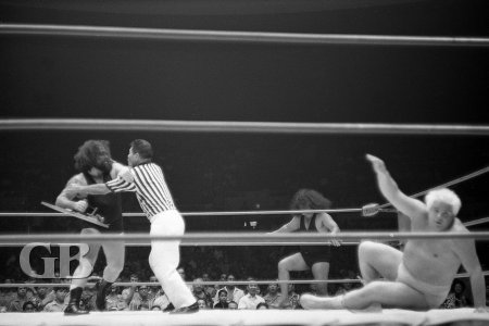 The Link threatens to hit Collins with a foreign object as referee Wally Tsutsumi tries to quell the situation.