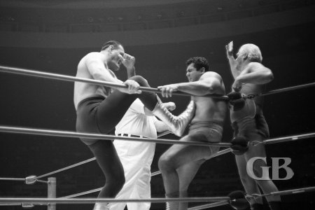 Killer Kowalski stomps away at Pedro Morales from inside the ring while Angelo Poffo works on Morales from the outside.