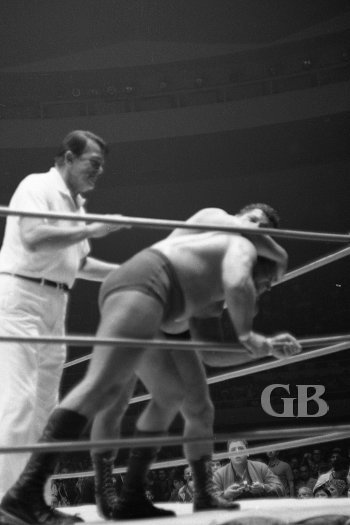 Referee Pete Peterson goes to break things up as Johnny Barend holds onto the ropes.