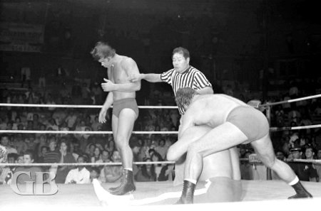 Ed Francis applies the sleeper hold onto Sweet Daddy Siki as son Billy walks by in a daze