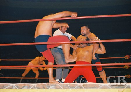 Mitsu Arakawa delivers a karate kick to Cyclone Negra as partner Kenji Shibuya holds on