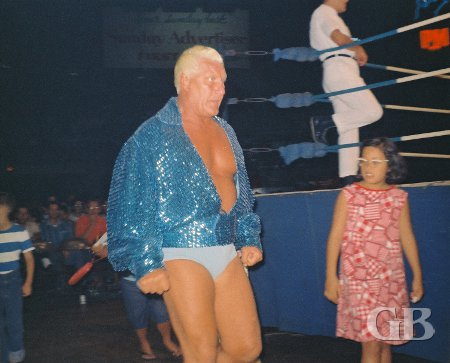 A young wrestling fan keeps her distance from a serious looking Blassie.