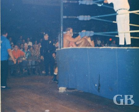 The four wrestlers battle outside the ring.