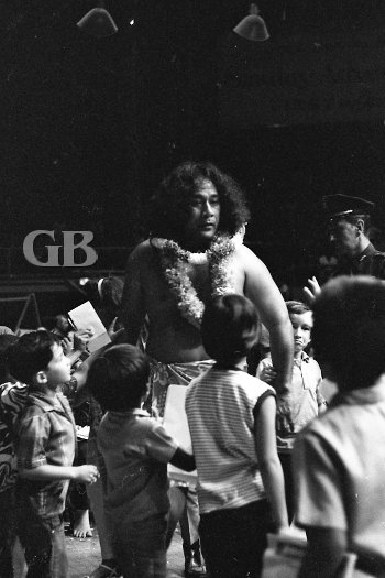 Neff Maiava approaches the ring surrounded by young wrestling fans.