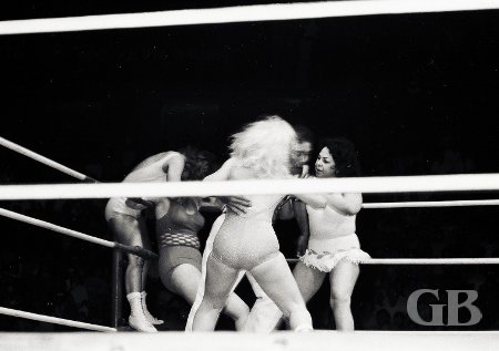 Referee Wally Tsutsumi separates Joyce Grable and Moolah as Betty Boucher works over Pat Sherry in the corner.