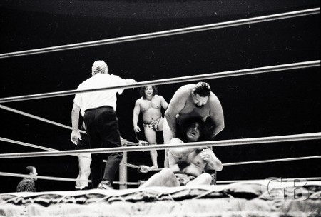 Curtis Iaukea applies a nerve hold on Neff Maiava as tag partner Peter Maivia stands on the ropes in the background.