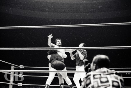Referee #1, Pete Peterson, looks on as the Missing Link applies his famous bearhug on Curtis Iaukea.