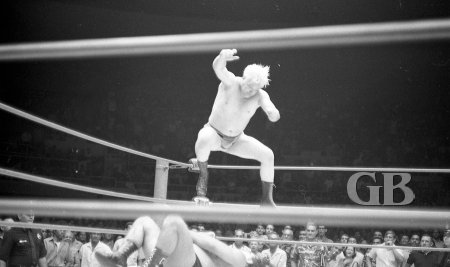 Ray Stevens delivers a knee drop onto a downed Jim Hady as the crowd rises to their feet.