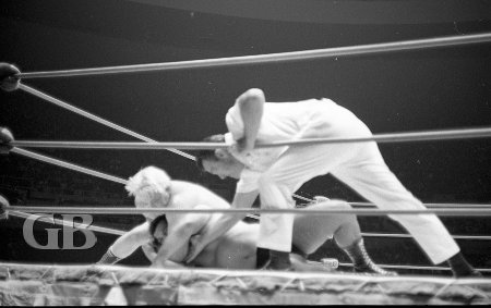 Referee Pete Peterson checks to see that Ray Stevens' head lock on Jim Hady is not a choke hold.