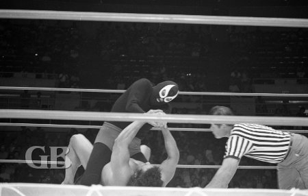 The Masked Executioner attempts to use his Claw Hold on Jimmy Snuka.
