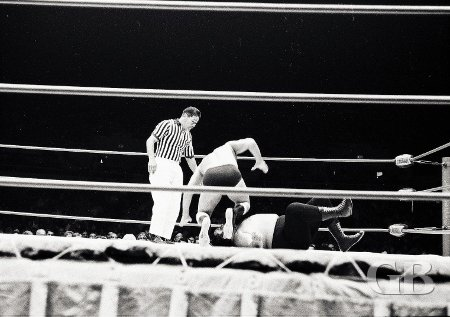 John Tolos drops a knee onto a downed Curtis Iaukea.