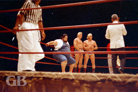 Haystacks Calhoun sits on the ropes while  Jim Lathrop announces the match.