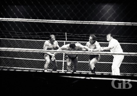Barend and Maurice about to throw Jim Hady into the ropes and metal fence.