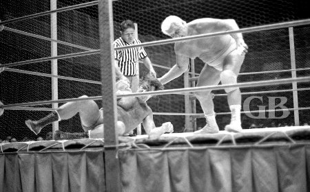 Fred Blassie works over Ed Francis in the chicken wire covered ring.