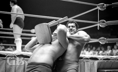 Pedro Morales chokes Nick Bockwinkel with a stool while outside the ring.