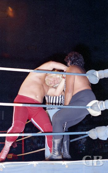 Maddog Mayne has Iaukea in the corner and prepares to work him over