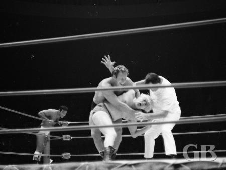 Bockwinkel applies the abdominal stretch on Patterson while White Wolf looks on.