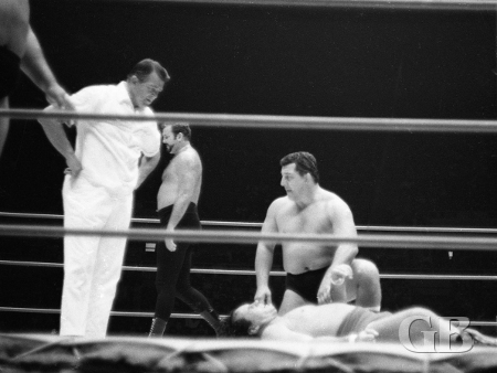 Hady kneels over Barend after losing the second fall. Referee Pete Peterson looks on.