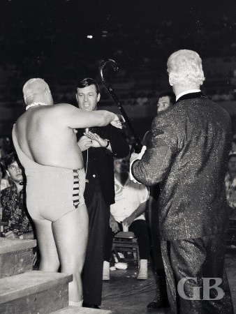 Ripper Collins argues with promoter Ed Francis and Jim Hady as valet Beauregarde (back to camera) watches.