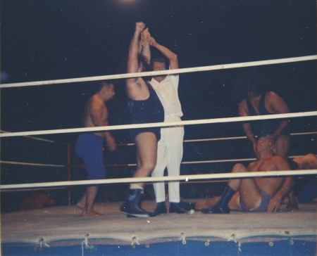 Referee Pete Peterson raises the Link's hand after his team won a fall as Neff Maiava tries to wake up Angelo Poffo in the background.