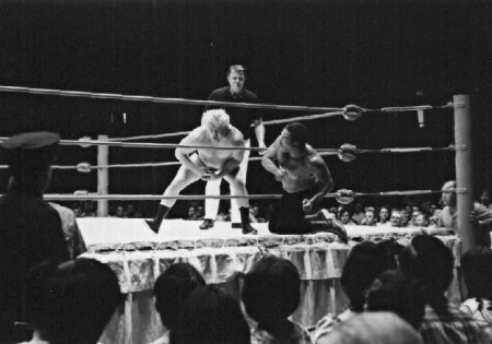 Rocky Montero works over Ray Stevens from outside the ring.