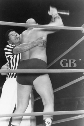 Referee Wally Tsutsumi prevents The Skull from using a foreign object against Karl Gotch.