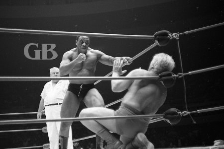 Sailor Art Thomas confronts a cowering Fred Blassie in the corner.